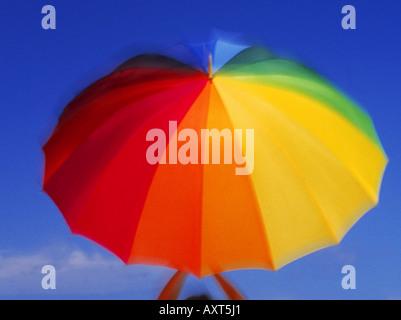 Bunte drehen Sonnenschirm gehalten von zwei Armen - Stockfoto