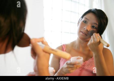 Asiatische Frau gilt Make-up, als sie in den Spiegel schaut. - Stockfoto