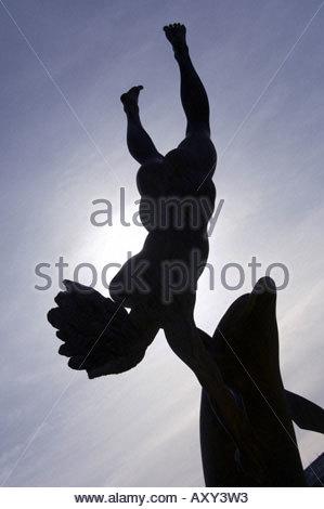 Statue des Mädchens mit Delphin Silhouette mit der Sonne im Hintergrund in der Nähe von Tower Bridge in London - Stockfoto
