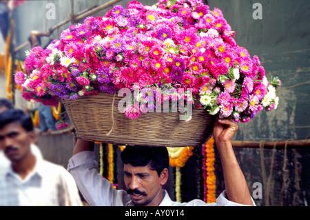 Ein Portier trägt einem Stock Korb mit einer duftenden Last auf Dadar Blumenmarkt den größten Großhandel Blumenmarkt - Stockfoto
