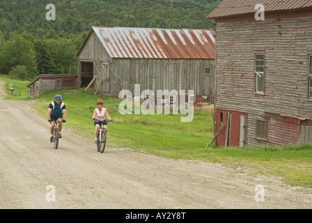 Paar Mountainbikes auf einem ländlichen Feldweg vorbei Reiten verwitterte Scheunen in Warren Vermont an einem bewölkten - Stockfoto