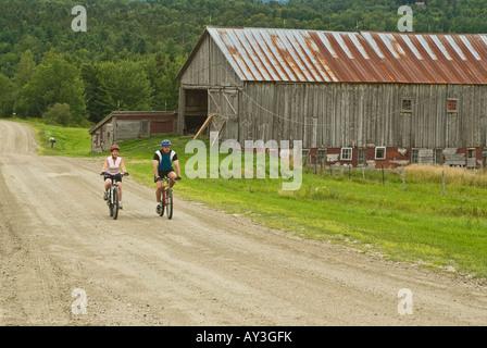 Paar Reiten Mountainbikes auf einem ländlichen Feldweg vorbei eine verwitterte Scheune in Warren Vermont an einem - Stockfoto