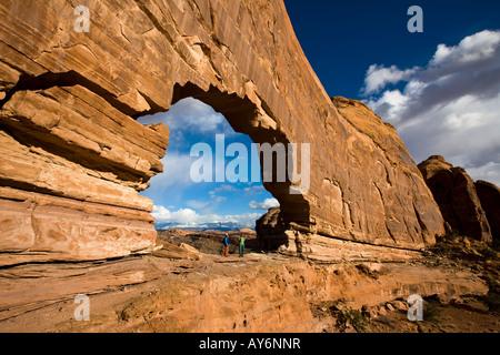 zwei Wanderer stehen unter Jeep Bogen in der Nähe von Moab Utah - Stockfoto