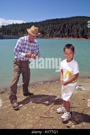 Herr 592 Großvater Bill McGill hilft Enkel Iasiah Soto mit seinem Fang von Forellen, am Angeltag in Ruidoso, New - Stockfoto