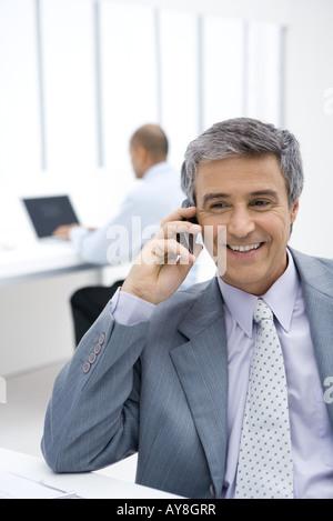 Geschäftsmann mit Handy im Büro - Stockfoto