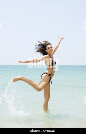 Junge Frau am Strand sprang, ein Bein, hob die Arme - Stockfoto