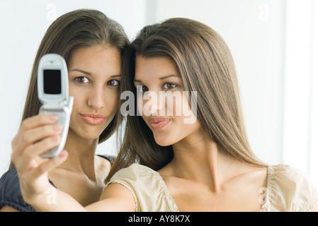 Teenager-Mädchen fotografieren selbst und Zwillingsschwester mit Handy, beide machen Gesichter - Stockfoto