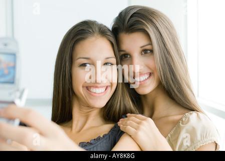 Teenager-Mädchen fotografieren selbst und Zwillingsschwester mit Handy, beide Lächeln - Stockfoto