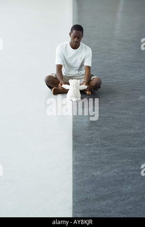 Teen Junge sitzt am Boden, spielen mit Stofftier - Stockfoto