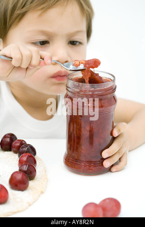 Kleiner Junge schöpfen Marmelade aus Glas mit Löffel, Torte und Kirschen auf Tisch vor ihm - Stockfoto