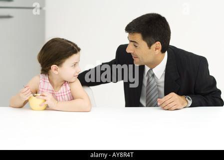 Vater und Tochter sitzen am Tisch, Blick auf einander, kleine Mädchen essen Müsli - Stockfoto