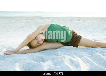 Kleines Mädchen tun Split am Strand, schiefen über, Arme heben, lächelnd in die Kamera - Stockfoto