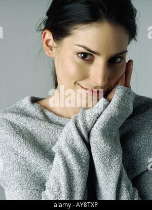 Frau lächelt in die Kamera, die Hände verschränkt neben Backe, Porträt - Stockfoto
