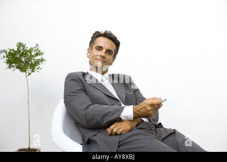 Geschäftsmann, sitzen, anhören von MP3-Player, lächelnd in die Kamera - Stockfoto