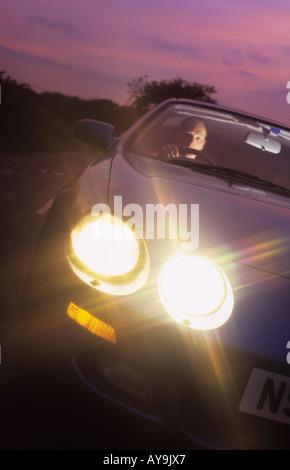 Mann fahren Auto auf Landstraße bei Sonnenuntergang Leeds Yorkshire uk - Stockfoto