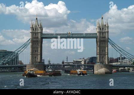 Themse in London und die Tower Bridge mit zwei Schlepper ziehen Schiffe beladen mit Containern voll von komprimierten - Stockfoto