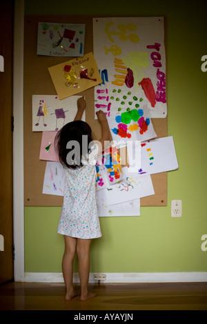 Vier Jahr setzt altes Mädchen ihr Kunstwerk auf eine Pinnwand - Stockfoto