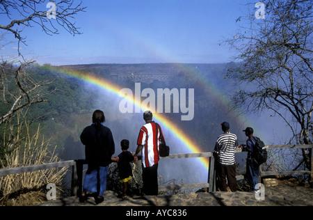 Menschen viel Freude beim Betrachten des doppelten Regenbogens in der Gischt der Victoriafälle aus Sambia Seite - Stockfoto