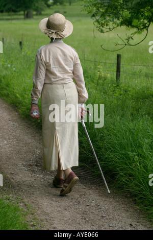 Englische Frau im Alter von siebziger Jahre geht in die englische Landschaft mit Gehstock - Stockfoto