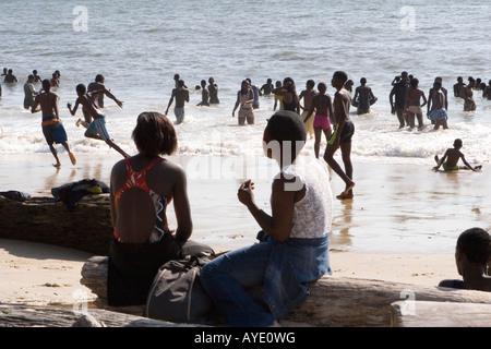 2 afrikanische Mädchen sitzen auf Protokolle am Strand, entspannen und beobachten der jungen vergehen, Libreville, - Stockfoto
