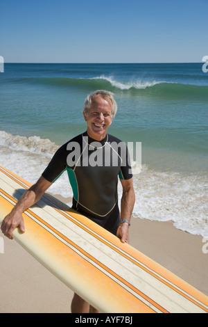 Man Holding Surfbrett am Strand - Stockfoto