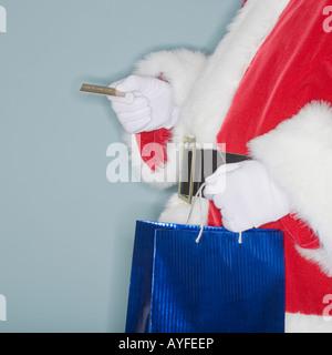 Santa Claus holding Einkaufstasche und Kreditkarte - Stockfoto
