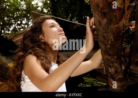 Junge Frau in einem zerstörten Holzhaus - Stockfoto