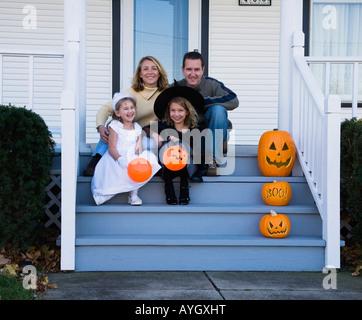Familie mit Töchtern in Hexe und Prinzessin Halloween-Kostüme gekleidet - Stockfoto