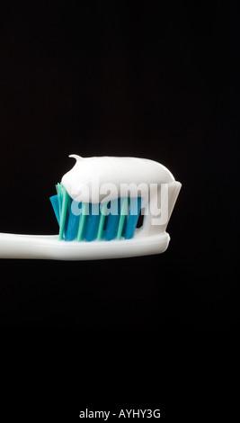 Zahnpasta frisch gepresst auf eine Zahnbürste mit schwarzem Hintergrund. Bild von Jim Holden. - Stockfoto