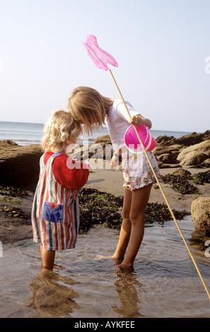 Junge Mädchen mit Fischernetzen zusammen zu spielen, an einem Strand in Cornwall im Vereinigten Königreich - Stockfoto