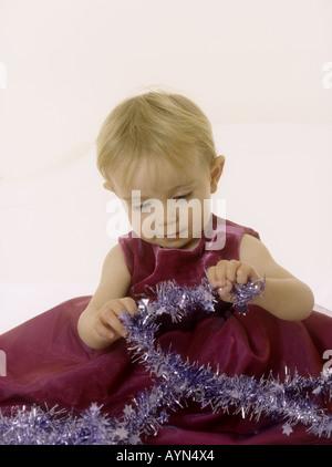Babymädchen trägt ein Partykleid Blick auf Lametta zu Weihnachten - Stockfoto