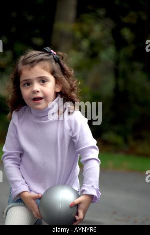 Drei Jahre altes Mädchen laufen und halten einen basketball - Stockfoto
