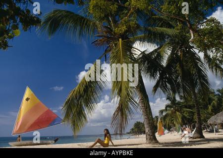 Dominikanische Republik West Indies Karibik Casa de Campo Las Minitas Beach mit Palmen gesäumt, Frau sitzt auf sand - Stockfoto