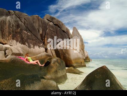 Frau, die Verlegung auf Felsen, Anse Source S'Argent Strand, La Digue Island, Seychellen, Afrika - Stockfoto