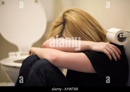 Nahaufnahme der Arme und Schultern der blonde junge Frau sitzt in der fetalen Position auf dem Boden der Toilette - Stockfoto