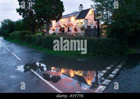 Das Brook Inn spiegelt sich in einer Pfütze auf der Straße in der Nähe von Feckenham Worcestershire UK - Stockfoto
