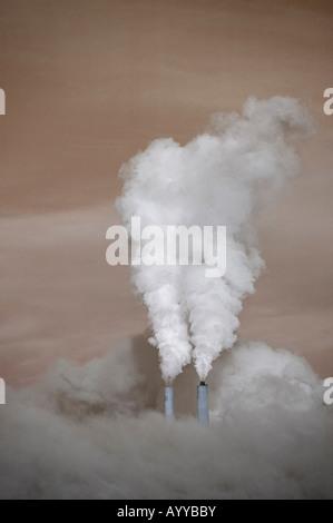 umgeben von einem braunen Dunst, strahlt ein Kohle-Verbrennung elektrischen Erzeugungsanlage Dampf aus den zwei - Stockfoto