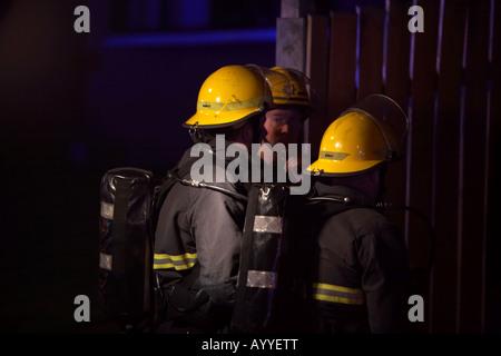 Feuerwehrleute tragen Helme Schutzkleidung und Atemschutz warten Zutritt in ein Wohnhaus Feuer Nacht - Stockfoto