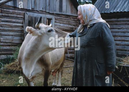 Russland, Kostroma District, Bäuerin mit ihrer Kuh - Stockfoto