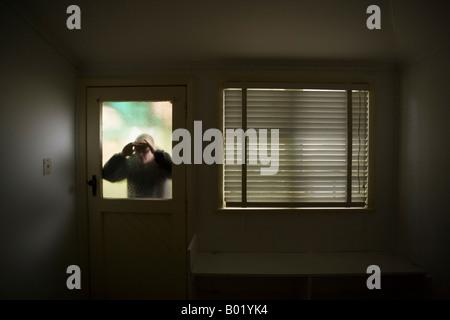 Mann sieht in Raum durch Milchglas Fensterscheibe an Tür neben Fenster mit Rollo - Stockfoto