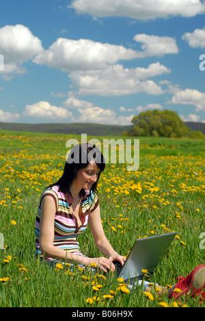 Frau auf einer wunderschönen Blumenwiese online arbeiten. - Stockfoto