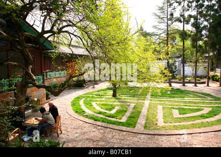Männer spielen Schach neben ornamentalen Rasenflächen im Black Dragon Pool Park. - Stockfoto