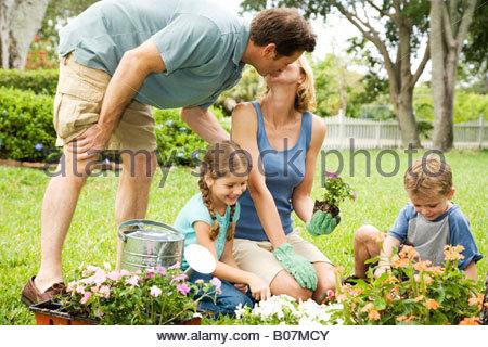 Gartenarbeit Familienvater Mutter küssen - Stockfoto
