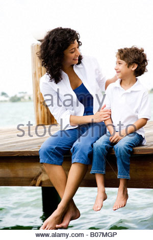 Mutter und Sohn sahen einander sitzen auf einem Steg - Stockfoto