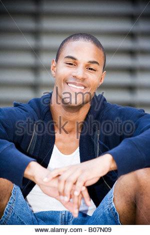 Porträt einer afroamerikanischen Jüngling sitzen lächelnd - Stockfoto