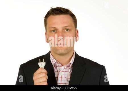 40 Jahre alte Geschäftsmann hält am Stecker und Buchse eines Kabels - Stockfoto
