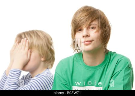 10 und 13 Jahre alten Jungen, 10-Year-Old bedeckte sein Gesicht mit den Händen - Stockfoto