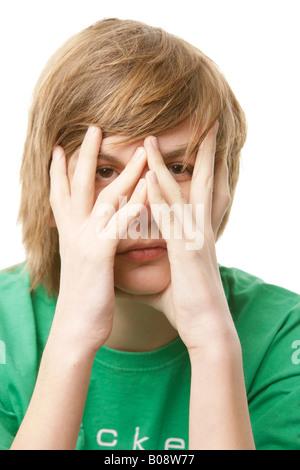 13-Year-Old Boy bedeckte sein Gesicht mit den Händen - Stockfoto