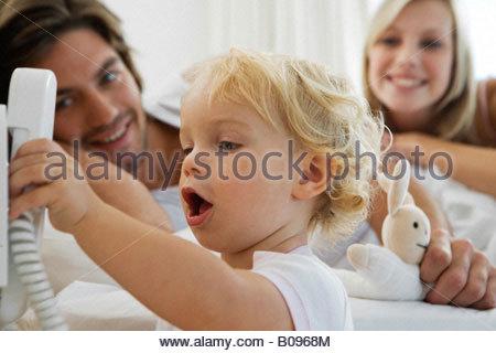 Baby (12-24 Monate) mit Telefon, junge Eltern, die gerade spielen - Stockfoto
