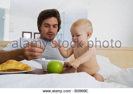 Junger Vater Fütterung Baby (6-12 Monate) im Bett - Stockfoto